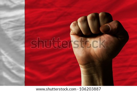 complete national flag of bahrain covers whole frame, waved, crunched and very natural looking. In front plan is clenched fist symbolizing determination - stock photo