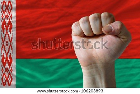 complete national flag of belarus covers whole frame, waved, crunched and very natural looking. In front plan is clenched fist symbolizing determination - stock photo