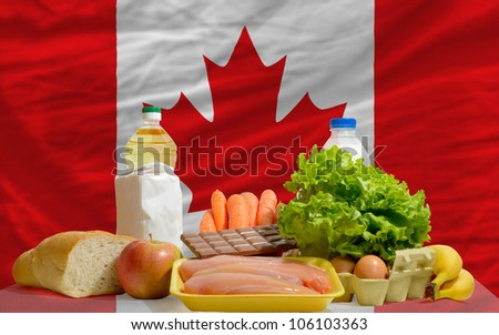 complete national flag of canada covers whole frame, waved, crunched and very natural looking. In front plan are fundamental food ingredients for consumers, symbolizing consumerism an human needs - stock photo