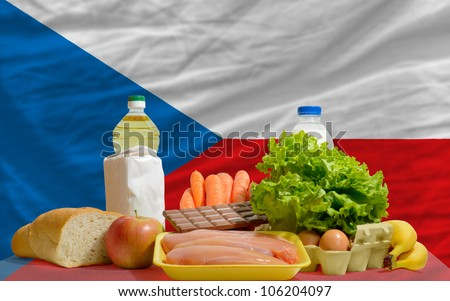 complete national flag of czech covers whole frame, waved, crunched and very natural looking. In front plan are fundamental food ingredients for consumers, symbolizing consumerism - stock photo