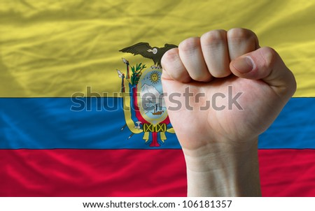 complete national flag of ecuador covers whole frame, waved, crunched and very natural looking. In front plan is clenched fist symbolizing determination - stock photo