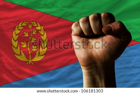 complete national flag of eritrea covers whole frame, waved, crunched and very natural looking. In front plan is clenched fist symbolizing determination - stock photo