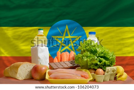complete national flag of ethiopia covers whole frame, waved, crunched and very natural looking. In front plan are fundamental food ingredients for consumers, symbolizing consumerism - stock photo