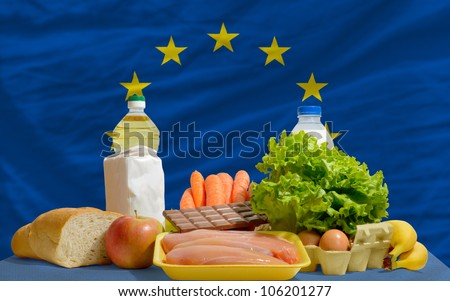 complete national flag of europe covers whole frame, waved, crunched and very natural looking. In front plan are fundamental food ingredients for consumers, symbolizing consumerism - stock photo