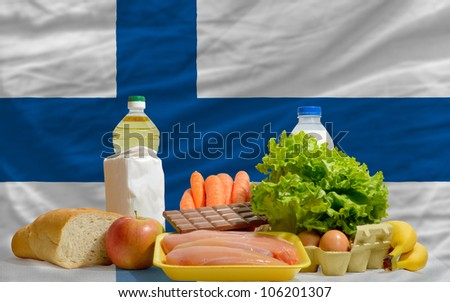 complete national flag of finland covers whole frame, waved, crunched and very natural looking. In front plan are fundamental food ingredients for consumers, symbolizing consumerism - stock photo