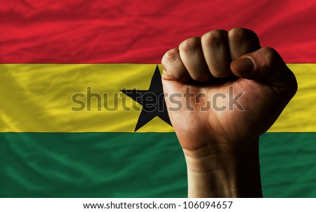 complete national flag of ghana covers whole frame, waved, crunched and very natural looking. In front plan is clenched fist symbolizing determination - stock photo