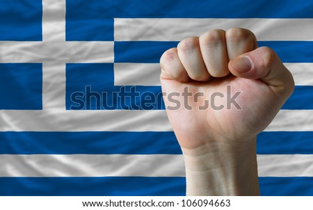 complete national flag of greece covers whole frame, waved, crunched and very natural looking. In front plan is clenched fist symbolizing determination - stock photo