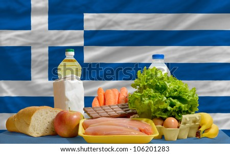 complete national flag of greece covers whole frame, waved, crunched and very natural looking. In front plan are fundamental food ingredients for consumers, symbolizing consumerism - stock photo
