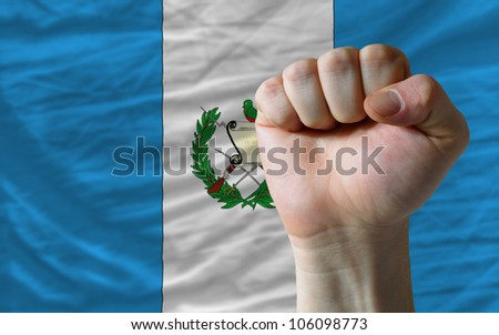 complete national flag of guatemala covers whole frame, waved, crunched and very natural looking. In front plan is clenched fist symbolizing determination - stock photo