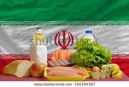 complete national flag of iran covers whole frame, waved, crunched and very natural looking. In front plan are fundamental food ingredients for consumers, symbolizing consumerism - stock photo