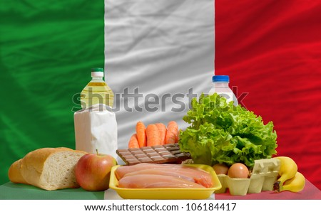 complete national flag of italy covers whole frame, waved, crunched and very natural looking. In front plan are fundamental food ingredients for consumers, symbolizing consumerism - stock photo