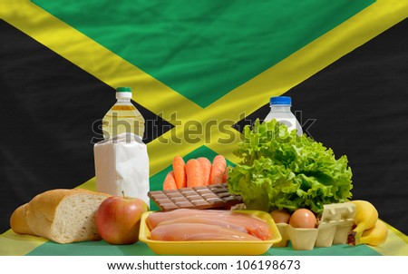 complete national flag of jamaica covers whole frame, waved, crunched and very natural looking. In front plan are fundamental food ingredients for consumers, symbolizing consumerism - stock photo