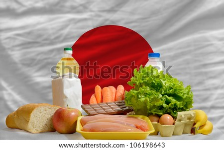 complete national flag of japan covers whole frame, waved, crunched and very natural looking. In front plan are fundamental food ingredients for consumers, symbolizing consumerism - stock photo