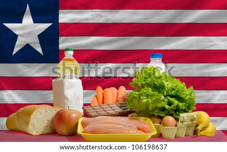 complete national flag of liberia covers whole frame, waved, crunched and very natural looking. In front plan are fundamental food ingredients for consumers, symbolizing consumerism - stock photo
