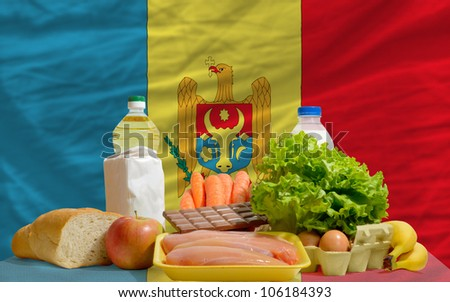 complete national flag of moldova covers whole frame, waved, crunched and very natural looking. In front plan are fundamental food ingredients for consumers, symbolizing consumerism - stock photo