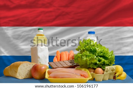 complete national flag of netherlands covers whole frame, waved, crunched and very natural looking. In front plan are fundamental food ingredients for consumers, symbolizing consumerism - stock photo