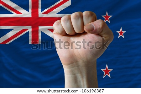 complete national flag of new zealand covers whole frame, waved, crunched and very natural looking. In front plan is clenched fist symbolizing determination - stock photo