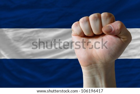 complete national flag of nicaragua covers whole frame, waved, crunched and very natural looking. In front plan is clenched fist symbolizing determination - stock photo