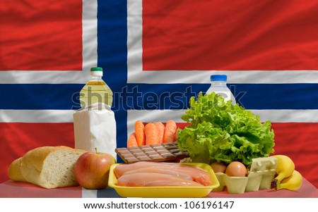 complete national flag of norway covers whole frame, waved, crunched and very natural looking. In front plan are fundamental food ingredients for consumers, symbolizing consumerism - stock photo