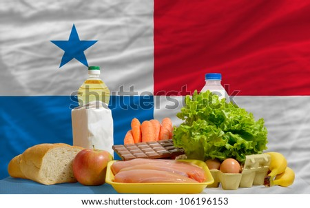 complete national flag of panama covers whole frame, waved, crunched and very natural looking. In front plan are fundamental food ingredients for consumers, symbolizing consumerism - stock photo