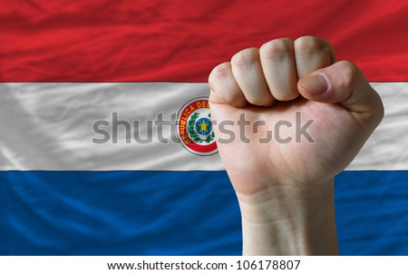 complete national flag of paraguay covers whole frame, waved, crunched and very natural looking. In front plan is clenched fist symbolizing determination - stock photo