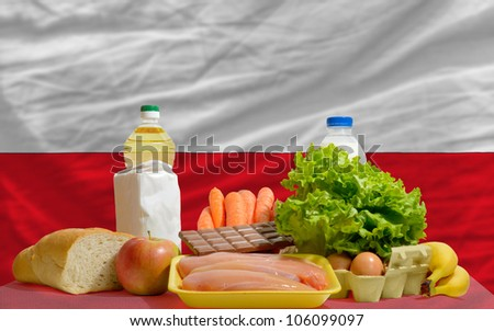 complete national flag of poland covers whole frame, waved, crunched and very natural looking. In front plan are fundamental food ingredients for consumers, symbolizing consumerism - stock photo