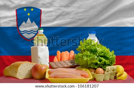 complete national flag of slovenia covers whole frame, waved, crunched and very natural looking. In front plan are fundamental food ingredients for consumers, symbolizing consumerism - stock photo