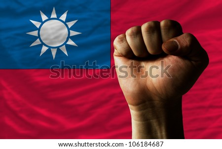 complete national flag of taiwan covers whole frame, waved, crunched and very natural looking. In front plan is clenched fist symbolizing determination - stock photo