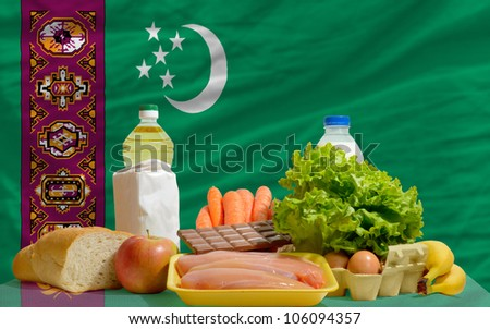 complete national flag of turkmenistan covers whole frame, waved, crunched and very natural looking. In front plan are fundamental food ingredients for consumers, symbolizing consumerism - stock photo
