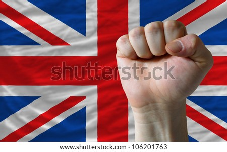 complete national flag of uk covers whole frame, waved, crunched and very natural looking. In front plan is clenched fist symbolizing determination - stock photo