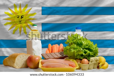 complete national flag of uruguay covers whole frame, waved, crunched and very natural looking. In front plan are fundamental food ingredients for consumers, symbolizing consumerism an human needs - stock photo