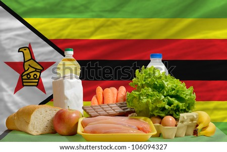 complete national flag of zimbabwe covers whole frame, waved, crunched and very natural looking. In front plan are fundamental food ingredients for consumers, symbolizing consumerism an human needs - stock photo
