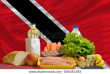 complete national flag trinidad tobago of covers whole frame, waved, crunched and very natural looking. In front plan are fundamental food ingredients for consumers, symbolizing consumerism - stock photo