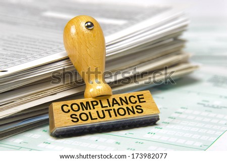 compliance solutions marked on rubber stamp - stock photo