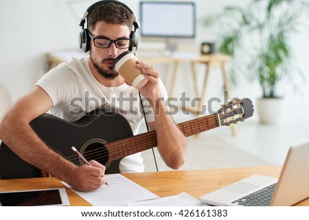 Composer drinking take-out coffee when working on new song - stock photo