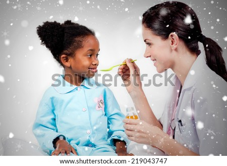 Composite image of adorable little girl taking medicine against snow falling - stock photo