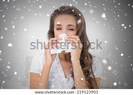 Composite image of attractive brunette blowing her nose against snow falling - stock photo