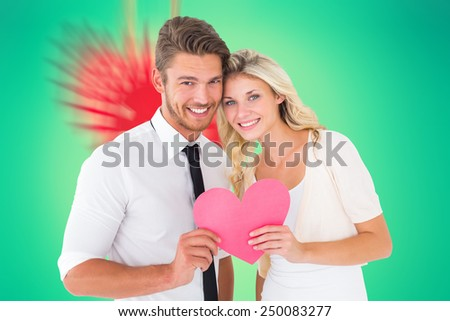 Composite image of attractive young couple holding pink heart - stock photo