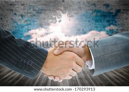 Composite image of business handshake against light shining into dark room - stock photo