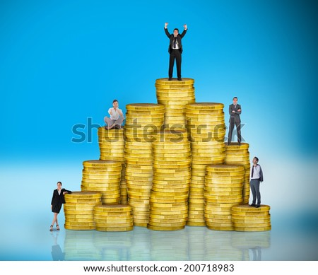 Composite image of business people on pile of coins against blue background with vignette - stock photo