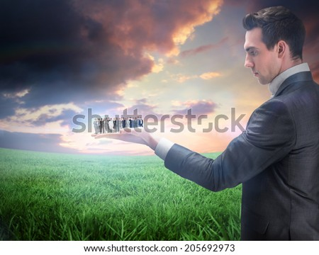 Composite image of businessman holding business team against green field under orange sky - stock photo