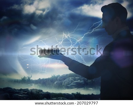 Composite image of businessman holding business team against stormy sky with tornado over landscape - stock photo