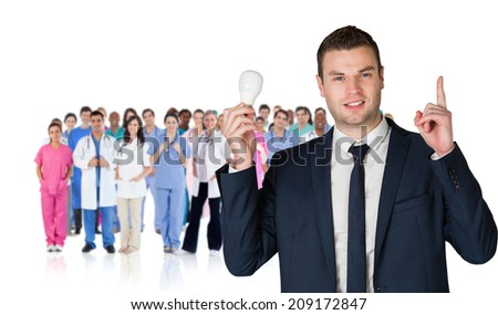 Composite image of businessman holding light bulb and pointing against group of workers - stock photo