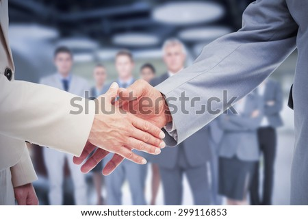Composite image of close up of business people shaking their hands - stock photo