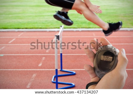 Composite image of coach is holding a stopwatch against selfassured male athlete jumping above hedge during a race - stock photo