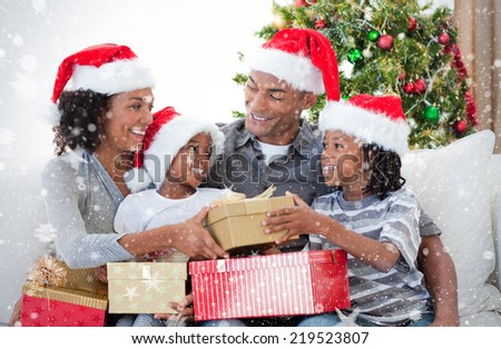 Composite image of Family celebrating Christmas at home against snow - stock photo