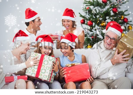 Composite image of Family swapping christmas presents against snow falling - stock photo
