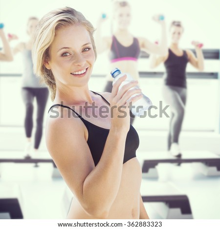 Composite image of fit blonde drinking water - stock photo