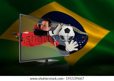 Composite image of fit goal keeper saving goal through tv against brazilian flag waving - stock photo