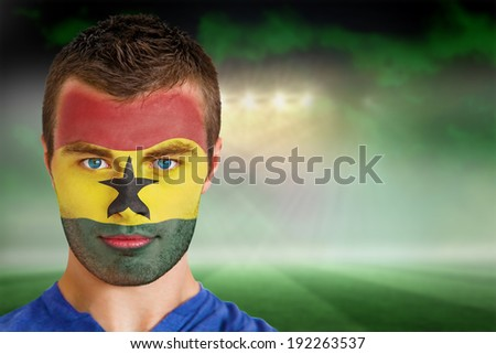 Composite image of ghana football fan in face paint against football pitch under green sky and spotlights - stock photo